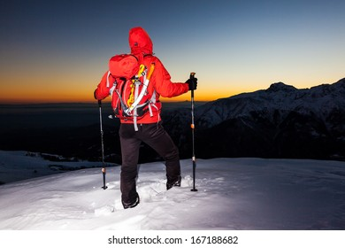 Winter hiking: man stands on a snowy ridge looking at the sunset (point-and-shoot camera style version). South Alps mountain  landscape. Italy, Europe.