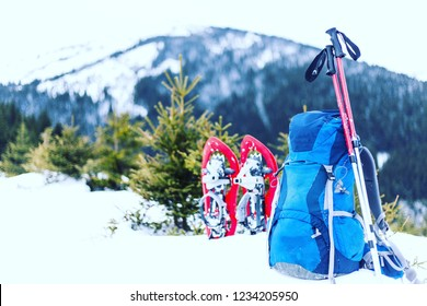Winter hiking in the mountains with a tent in snowshoes.