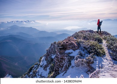 Winter hiking theme. Hiker standing on the top of hill. Tourist hiker with backpack standing on rocky mountain, snow capped hills are in the background. Chočské mountains, South Orava, Central Europe