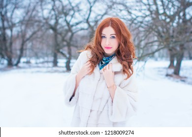Winter holiday concept. Inspiration and fairy cold time. Woman in fashionable dress and fur coat at park . Pretty nice lady outdoor, holiday days, snowy magical christmas time