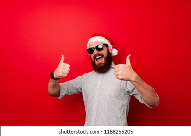Winter holiday and countdown concept. Man with beard and cheerful face celebrates Christmas. Santa Claus waits for New Year on red background. Santa showing thumbs up