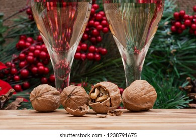 Winter holiday decoration: Blooming Red Poinsettia, Pine, Berry bush, walnuts and two glasses of white wine on wooden background