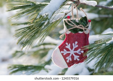 Winter holiday decoration concept: snowflake crochet Christmas stocking and frozen snow covered pine tree twigs in forest preserve park.
