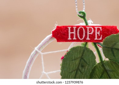 Winter holiday decoration:  dream catcher with green leaves, sign hope and Christmas tree ball on burlap background