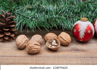 Winter holiday decoration: green garland, Christmas tree ball, pine cone and walnuts on wooden background