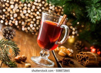Winter holiday hot alcohol drink. Mulled wine with fruits and spices by Christmas tree.
