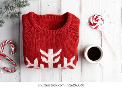 Winter holiday knitted sweater, hot coffee and lollipops on white wooden background