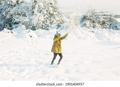 winter holiday.Happy childhood. girl green jackets gray winter hats in the forest runs plays and throws snow