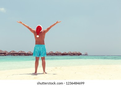 Winter holidays celebration on tropical beach, man on beach in Santa hat with outstreched arms, enjoying Christmas vacation, warm toned greeting card