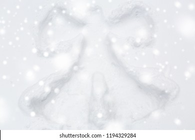 winter holidays and christmas concept - angel silhouette or print on snow surface