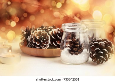 Winter holidays christmas decor. Glass jars with natural pine cones, candle lights background, bokeh effect.