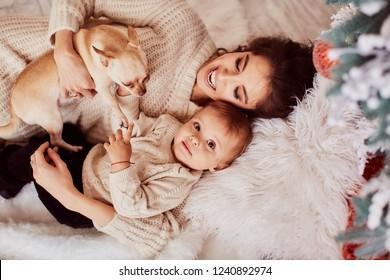 Dekoration für Winterferien. Warme Farben. Familienporträt. Adable Mama und Tochter haben Spaß beim posieren vor einem reichen, dekorierten Weihnachtsbaum in einem gemütlichen Raum, der kleine Hunde auf den Armen hält