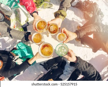 winter holidays - group of friends drinking beer on break at ski resort
