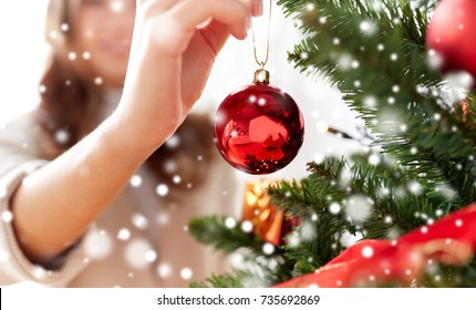 winter holidays and people concept - close up of young woman hand decorating christmas tree with red ball over snow