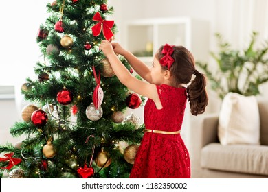 winter holidays and people concept - happy little girl decorating christmas tree at home