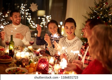 winter holidays and people concept - happy friends with sparklers celebrating christmas at home feast - Shutterstock ID 1186831723