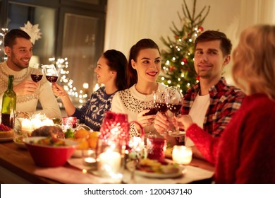 winter holidays and people concept - happy friends celebrating christmas at home feast and drinking red wine