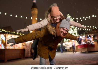 winter holidays and people concept - happy young couple dating and having fun at christmas market in evening