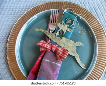 Winter holidays place setting with blue midcentury modern china on gold charger with festive napkin, ribbon and deco deer ornament. Blue rattan background.