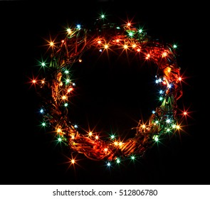 Winter holidays template card with copyspace isolated on black background. Wreath and garlands of colored light bulbs. Concept frame for shops label circle place for best price.