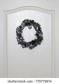 Winter holidays Wreath  on white wood door.  Wreath of light tone and garlands of natural silvery fir cones.