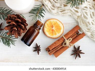 Winter home fragrances blend. Essential oils, orange, cinnamon sticks, anise, fir, cones, woolen blanket, top view. Home spa treatment.