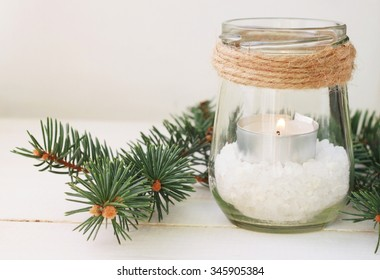 Winter home relaxing time. Pretty homemade candle holder - tea light in jar with salt and green pine boughs. Rustic style table decor