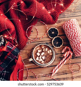 Winter homely scene. Warm knit sweater and cup of hot cocoa with marshmallows. Christmas lollipop, led lights string and other holiday decor.