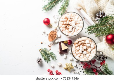 Winter hot drink. Christmas hot chocolate or cocoa with marshmallow on white with christmas decorations. Top view with copy space.