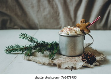 Winter hot drink with gingerbread men cookie and fir branch on the wooden white table.
