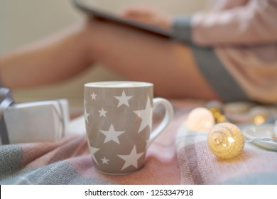 Winter hot drinks. Close up cup of coffee or hot chocolate. Blurred image womam in warm pink sweater with laptop, home comfort and relax. Christmas holidays, hot drinks and people concept.