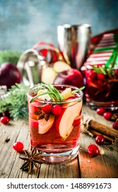 Winter hot sangria cocktail with red apples, wine, cranberry, rosemary and spices, christmas wooden background copy space
