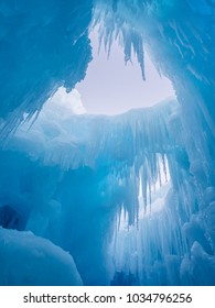 Winter ice cave with frozen icicles at sunset.