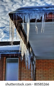 Winter icicles hanging from eaves of roof