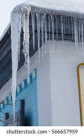 Winter icicles hanging on country house roof