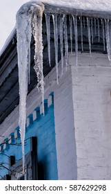 Winter icicles hanging on country house roof.