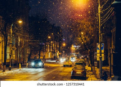 Winter illuminated city street or road with car traffic in snowy weather in night, toned