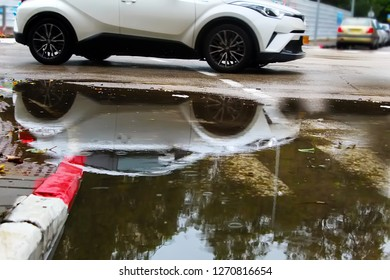 Winter in Israel: cold weather, rain, flood. Reflection of a passing car in a puddle of rainwater. Raindrops, circles on the water