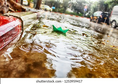 Winter in Israel, December. Paper Boat (Origami Ship) sails in a puddle during the rain, raindrops and circles on the water