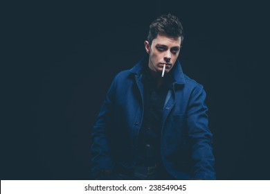 Winter jeans fashion man with short dark hair smoking a cigarette. Wearing blue jeans and jacket. Studio shot against black.