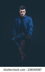 Winter jeans fashion man with short dark hair. Wearing blue jeans, jacket, brown leather boots and gloves. Sitting on old wooden box. Studio shot against black.