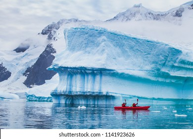 winter kayaking in Antarctica, extreme sport adventure, people paddling on kayak near iceberg