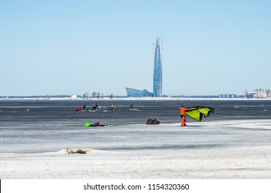 Winter kitesurfing on the frozen sea bay. A man kitesurfer is preparing for the flight. Preparation for kitesurf. The athlete's bright suit. Saint Petersburg, Russia, the Gulf of Finland, May 1, 2018