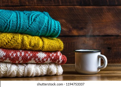 Winter, knitted sweaters and a mug of hot cocoa on a wooden background. Winter clothes. Ugly Christmas Sweater