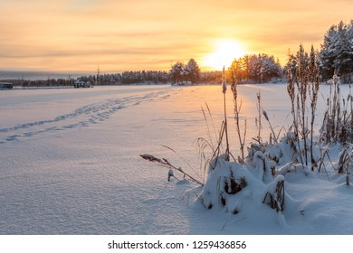Winter lake shore under ice and snow at sunset light, footsteps on snowy surface. Northern Karelia, copyspace