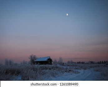 Winter landscape with an abandoned small dilapidated shack. The frozen field, the moon. Beauty of nature in winter