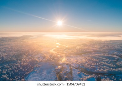 Winter landscape aerial drone view. Blue sky over scenic frosty meadow with river. Winter sunrise.