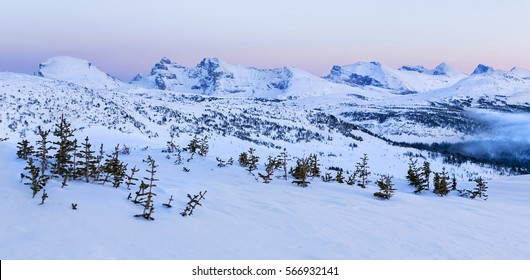 Winter Landscape Alpenglow over Distant Snowy Mountain Tops on Healy Pass after Banff National Park Sunset in Canadian Rocky Mountains