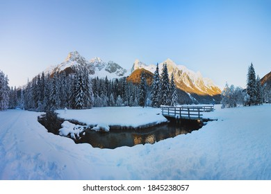 Winter landscape in the Alps, Christmas card view. Lake Antholz (Anterselva) at sunset, Dolomites, Italy. The river against the background of snow-covered peaks.