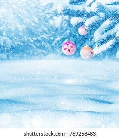 Winter landscape. Christmas balls on coniferous branch in  snow-covered forest. Winter background.